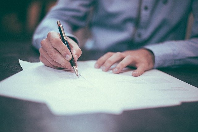 Muž podepisuje smlouvu