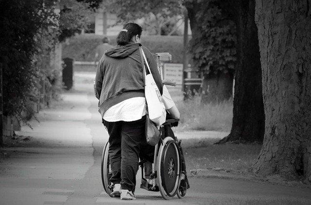 žena vezoucí invalidní vozík